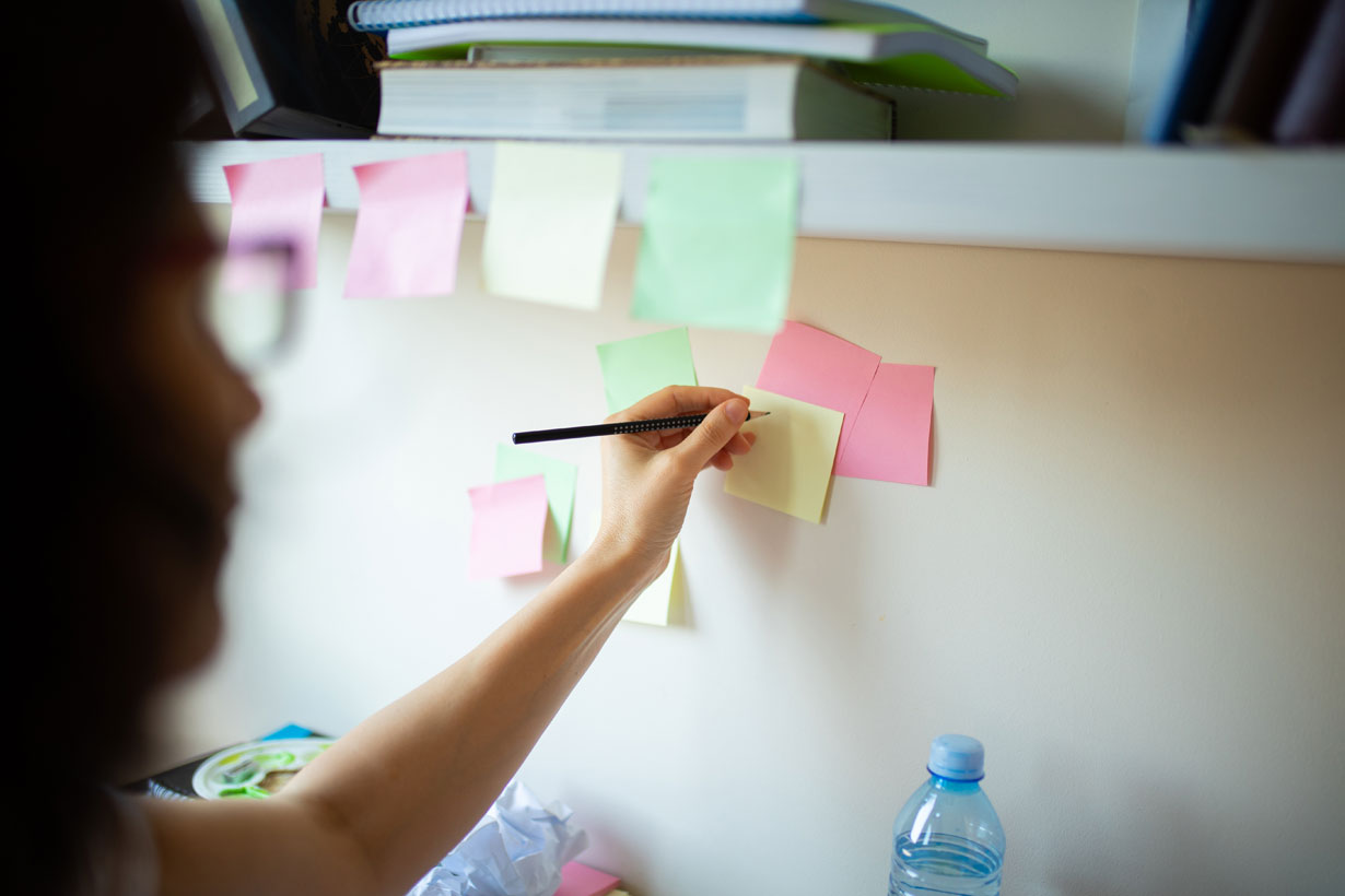 Woman writing on sticky notes on wall