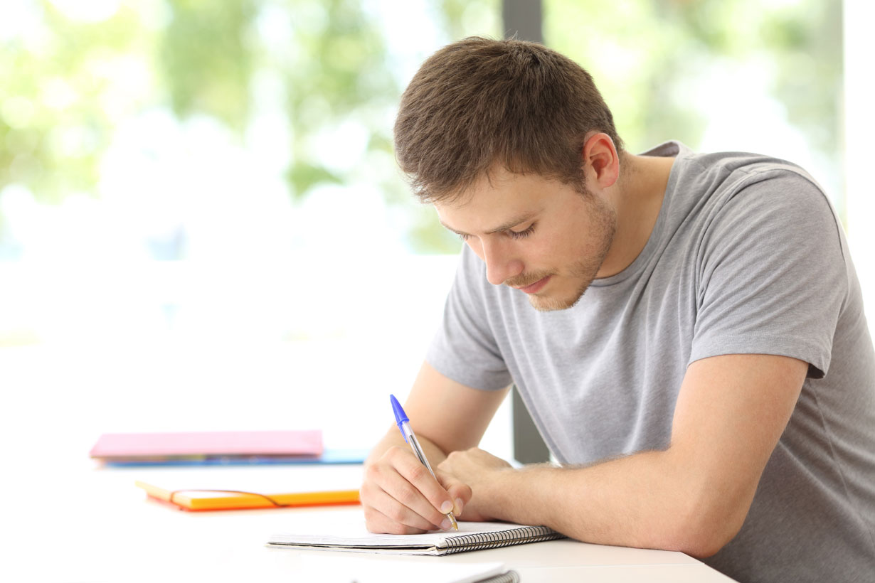 Man sat writing in a notebook