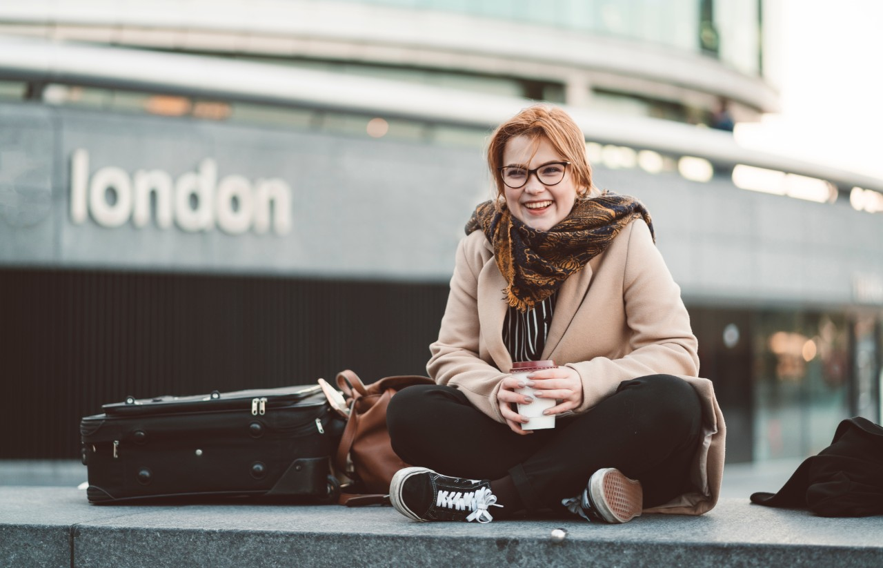 Young woman sat outside a london train station