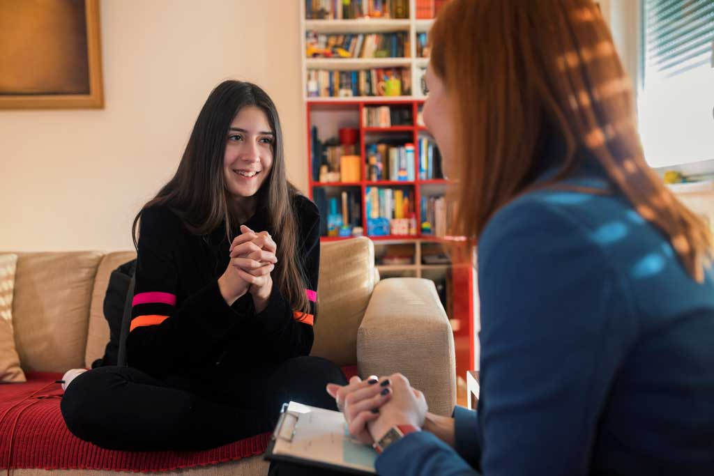 Teenage girl talking to nurse at home
