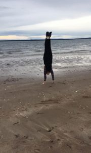Ally doing a handstand on the beach